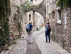 An unidentied couple explore the medieval Upper Town of Vaison-la-Romaine in the Vaucluse district of Provence, France.