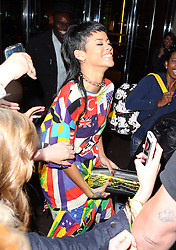 Singer Rihanna wearing a flag suit and carrying a Vivienne Westwood clutch bag with a gold penis on it, jokes around with the bag as she leaves her hotel in London, UK. 11/09/2013<br />