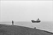 Nederland, Vlissingen, 15-11-1985Beeld van de Westerschelde vanaf de kade.Een man laat zijn hond uit en een vrachtschip vaart op het water.Foto: Flip Franssen/Hollandse Hoogte