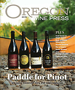 Bottles of Cramoisi Pinot Noir, Winderlea Pinot Noir, Yamhill Valley, and Arcane Cellars on a canoe paddle in front of a canoe on the banks of the Willamette River as part of the Pinot Paddle put on by Wiallmetter River Keepers