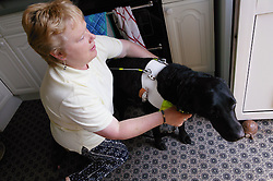 Partially sighted woman preparing guide dog for an outing,