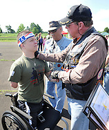 WARMINSTER, PA - JUNE 14: Marine Corporal Tyler Southern (L) is greeted by Lee Cannon of Newtown, Pennsylvania during the Wounded Hero 5K to support the Honor & Courage Program of Operation Ward 57 June 14, 2014 at Warminster Community Park in Warminster, Pennsylvania. Southern was on his second deployment when he lost both of his legs above the knees, his right arm above the elbow, and shattered his left arm and hand after stepping on an IED in Musa Qala in the Now Zad District of Afghanistan on May 5, 2010. (Photo by William Thomas Cain/Cain Images)