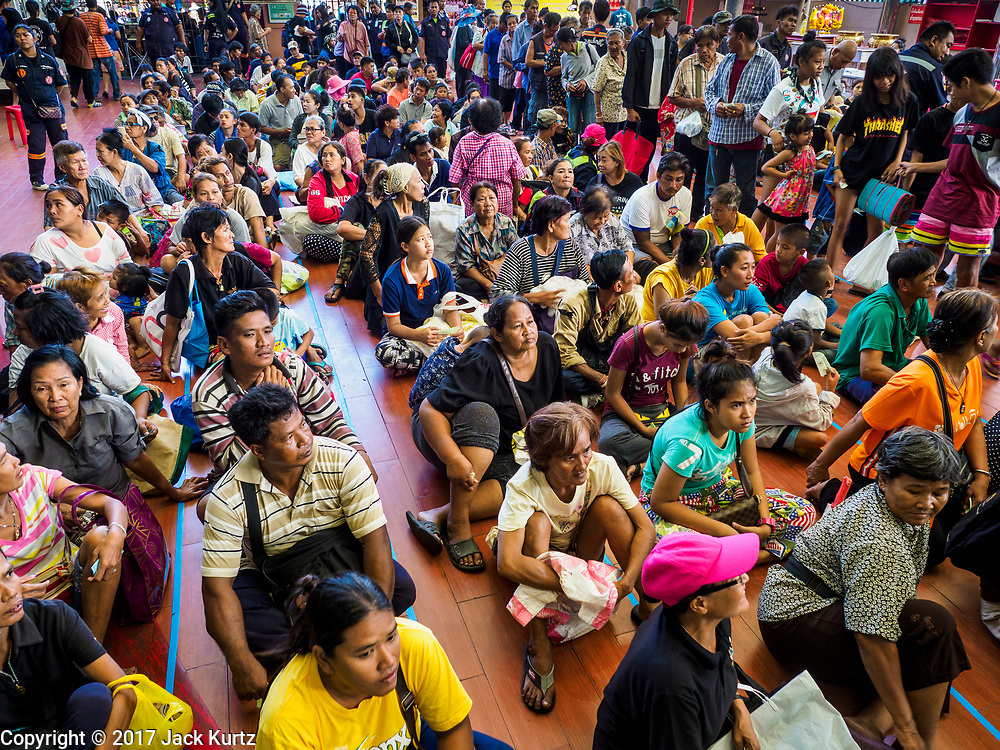 18 SEPTEMBER 2017 - BANGKOK, THAILAND: People in line for the food distribution at Poh Teck Tung in Bangkok on the last day Hungry Ghost Month. The Ghost Festival, also known as the Hungry Ghost Festival, Zhongyuan Festival or Yulan Festival is a traditional Buddhist and Taoist festival held in Asian countries. According to the Chinese calendar (a lunisolar calendar), the Ghost Festival is on the 15th night of the seventh month. In Chinese culture, the fifteenth day of the seventh month in the lunar calendar is called Ghost Day and the seventh month in general is regarded as the Ghost Month, in which ghosts and spirits, including those of the deceased ancestors, come out from the lower realm. Distinct from both the Qingming Festival (in spring) and Double Ninth Festival (in autumn) in which living descendants pay homage to their deceased ancestors, during Ghost Festival, the deceased are believed to visit the living.     PHOTO BY JACK KURTZ