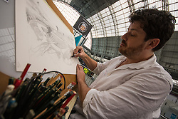 Olympia, London, August 9th 2015. Hundreds of real ale lovers attend the Campaign for Real Ale  Great British Beer Festival at London's Olympia Exhibition Centre, where dozens of independent breweries demonstrate the diversity of British brewed beers. PICTURED: Artist Malcolm Trollope-Davis works on a drawing for a Lewes based brewery's beer labels