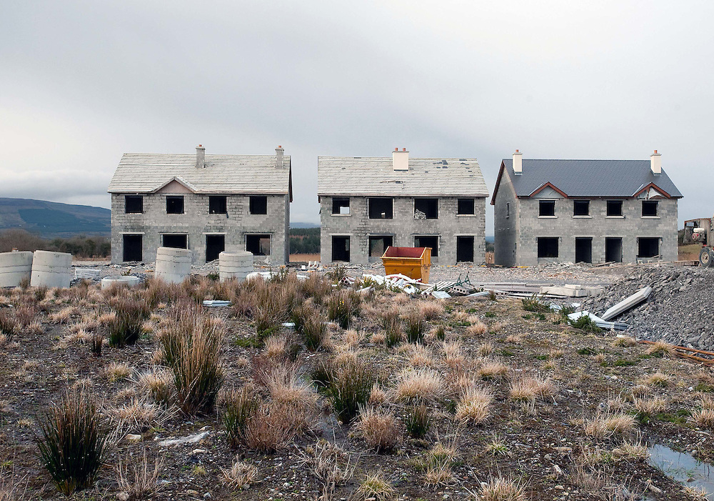 """Unfinished houses in """"Waterways"""" an ambitious development of 60 houses and 16 apartments along the Shannon-Erne waterway in the small village of Keshcarrigan, Co Leitrim where the advertising hoarding boasts of """"boating from your backyard"""" The development was launched in 2008 but is now a ghost estate. PHOTO © KIM HAUGHTON"""