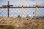 19 DECEMBER 2008 -- NOGALES, SON, MEX:    Crosses on the Mexican side of the border fence serve as a memorial for people who died trying the US. The buildings in the background are the Mariposa Port of Entry in Nogales, AZ.  PHOTO BY JACK KURTZ