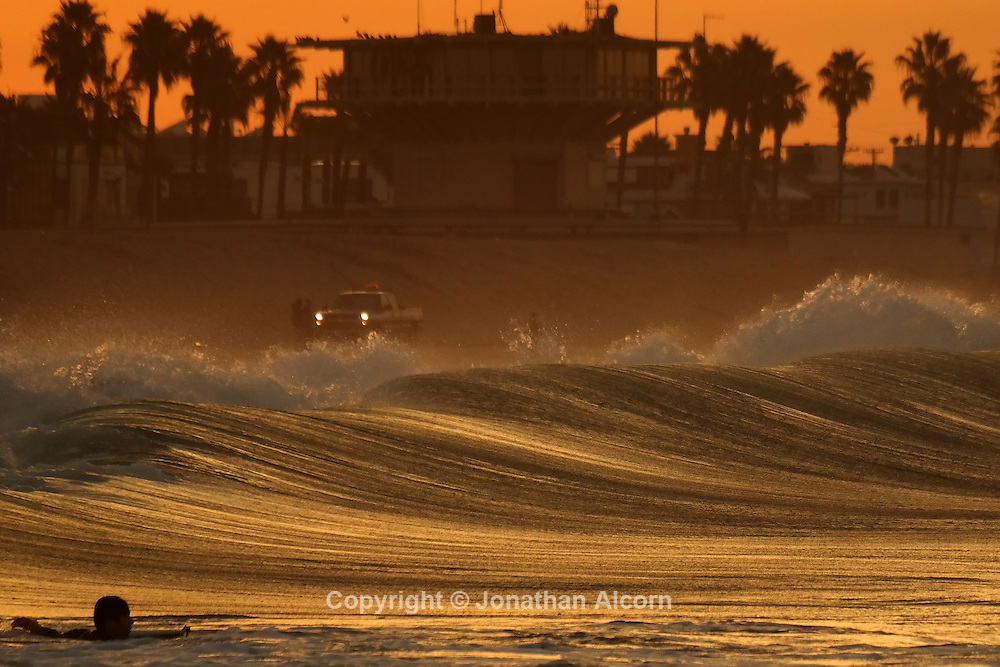 A wave breaks at sunrise in Venice Beach, California