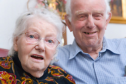Elderly Carer sitting on the settee with wife who has Alzheimer's disease,
