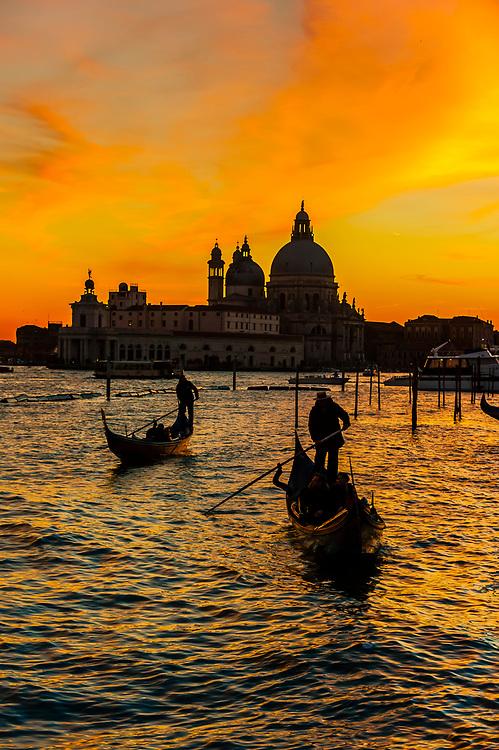 Gondolas cross the Venice Lagoon with Basilica di Santa Maria della Salute in background, Venice, Italy.