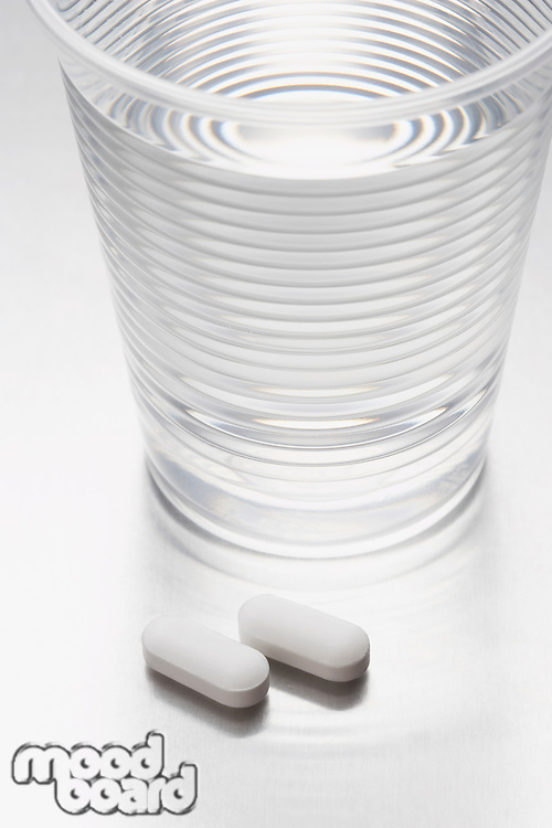 Two pills beside water in plastic cup
