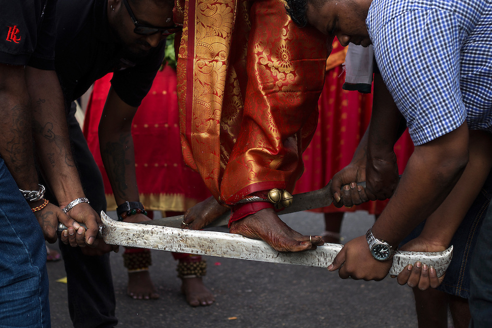 HIndu devotee walk on  a large heavy knife as he walk to the Batu Cave temple during a Thaipusam festival in Kuala Lumpur, Malaysia, 03 Fenruary 2015.  Thousands of Hindus gather to participate in the annual Thaipusam festival dedicated to Lord Murugan. During Thaipusam day, devotees will fulfilled their vows by carrying 'kavadi (bearers had spikes pierced into their bodies) or pots of milk as offering to Lord Murugan. The devotees will make the arduous climbing up the 272 steps leading up to the temple cave and deposited at the feet of the deity to purify themselves.