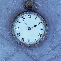 Pocket watch with white face and Roman numerals in block of ice