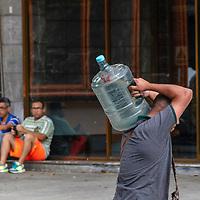Un hombre lleva una botella de agua. El mega apagón generó una crisis sin precedentes en el suministro de agua al país. A man carries a bottle of water. The mega blackout generated an unprecedented crisis of water supply to the country.