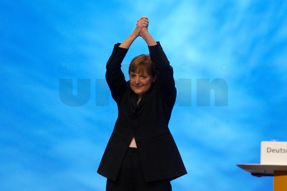 01 DEC 2003, BERLIN/GERMANY:<br /> Angela Merkel, CDU Bundesvorsitzende, haelt nach ihrer Eroeffnungede die Haende mit der Geste der Siegerin ueber den Kopf, waehrend die Delegierten ihr minutenlang applaudieren, 17. CDU Parteitag, Messe Leipzig<br /> IMAGE: 20031201-01-082<br /> KEYWORDS: party congress, Eröffnungsrede,  Applaus, Freude, Jubel, Sieg
