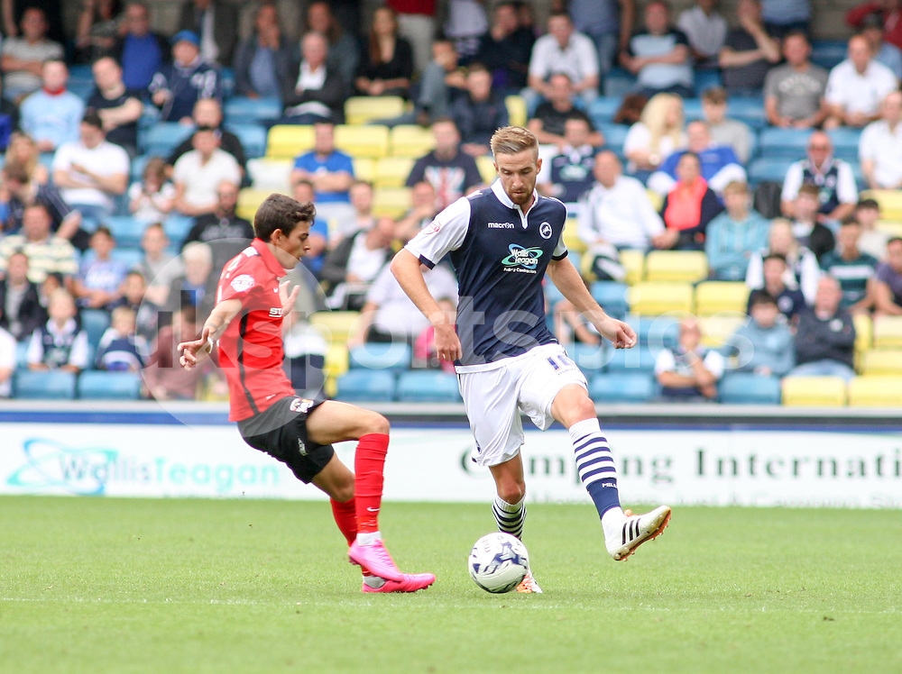 Mark Beevers of Millwall plays the ball past Ruben Lameiras of Coventry City during the Sky Bet League 1 match between Millwall and Coventry City at The Den, London, England on 15 August 2015. Photo by Edmund  Boyden.