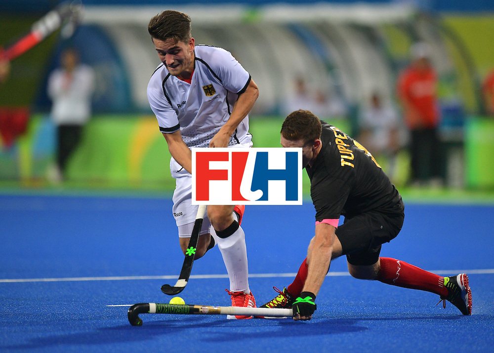 Germany's Moritz Trompertz fights for the ball with Canada's Scott Tupper during the men's field hockey Canada vs Germany match of the Rio 2016 Olympics Games at the Olympic Hockey Centre in Rio de Janeiro on August, 6 2016. / AFP / Carl DE SOUZA        (Photo credit should read CARL DE SOUZA/AFP/Getty Images)