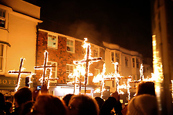 © Licensed to London News Pictures. 04/11/2017. Lewes, UK. People in costume carry burning crosses as they take part in celebrations for the traditional Lewes Bonfire Night celebrations on Saturday, 4 November, 2017. Thousands of people attend the parade through the narrow streets of Lewes and burn effigies to celebrate Guy Fawkes nightalso known as bonfire night, the anniversary of the gunpowder plot to blow up the Houses of Parliament in London. Photo credit: London News pictures