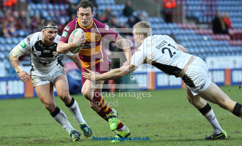 Picture by Stephen Gaunt/Focus Images Ltd +447904 833202.16/03/2013.Shaun Lunt of Huddersfield Giants on the attack  beats the tackle of Chris Green of Hull Football Club during the Super League match at the John Smiths Stadium, Huddersfield.
