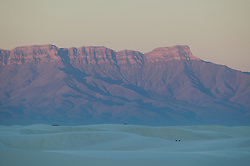 The red mountains in the distance contrast with the pale, white sand in White Sands National Monument, New Mexico.