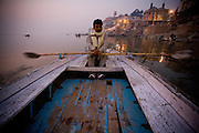 Varanasi. A boatman rows his boat on an ealry morning tourist ride on the Ganges.
