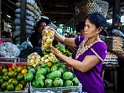 07 AUGUST 2017 - BEBANDEM, BALI, INDONESIA: A woman buys fruit in the market in Bebandem, in far eastern Bali. The market is known for baskets, which are woven in the area. Bali's local markets are open on an every three day rotating schedule because venders travel from town to town. Before modern refrigeration and convenience stores became common place on Bali, markets were thriving community gatherings. Fewer people shop at markets now as more and more consumers go to convenience stores and more families have refrigerators.     PHOTO BY JACK KURTZ