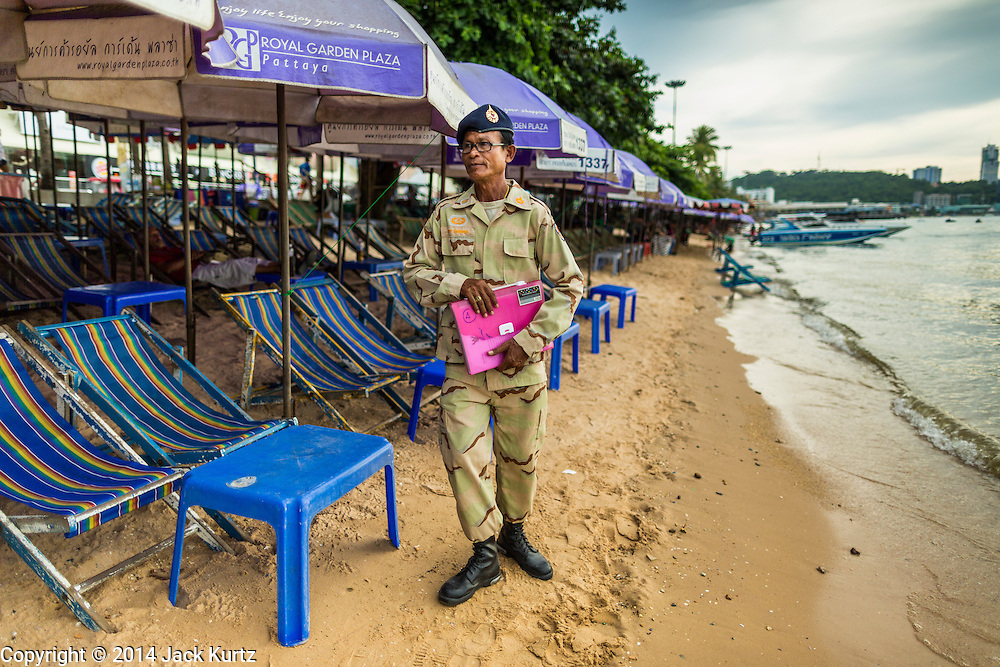 """26 SEPTEMBER 2014 - PATTAYA, CHONBURI, THAILAND: A defense volunteer checks on a business that rents beach umbrellas to tourists in Pataya. Pataya, a beach resort about two hours from Bangkok, has wrestled with a reputation of having a high crime rate and being a haven for sex tourism. After the coup in May, the military government cracked down on other Thai beach resorts, notably Phuket and Hua Hin, putting military officers in charge of law enforcement and cleaning up unlicensed businesses that encroached on beaches. Pattaya city officials have launched their own crackdown and clean up in order to prevent a military crackdown. City officials have vowed to remake Pattaya as a """"family friendly"""" destination. City police and tourist police now patrol """"Walking Street,"""" Pattaya's notorious red light district, and officials are cracking down on unlicensed businesses on the beach.     PHOTO BY JACK KURTZ"""