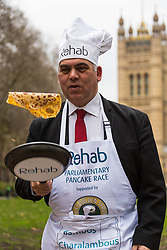MPs and members of the House of Lords compete in the annual Rehab pancake race, a relay of eleven laps in Victoria Tower Gardens adjacent to the Houses of Parliament in London. The race is held every year on Shrove Tuesday and was won by the Media team. PICTURED: Bambos Charalambous MP. London, February 13 2018.