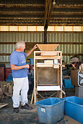 Frank Morton discussing the newly engineered seed thresher at his Wild Garden Seed farm.