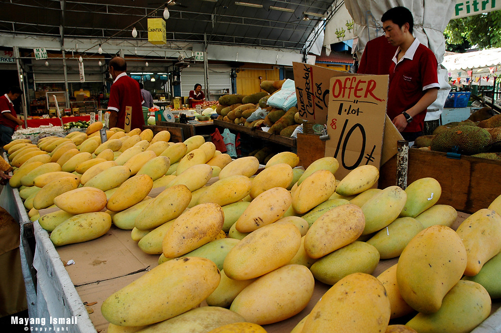 Fruit vendors selling mangoes in Geylang fruit market, Singapore