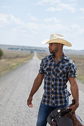 cowboy with a saddle on a dirt road