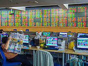 02 SEPTEMBER 2013 - BANGKOK, THAILAND:  A woman reads the newspaper in the stock ticker room at Asia Plus Securities headquarters in central Bangkok. The Thai stock market has declined more than 20% from its 2013 high as data as Thailand entered a recession in the second quarter. The loss of value in the Stock Exchange of Thailand (SET) is the greatest sell off since the end of the Asian financial crisis in 1998. Foreign investors have sold more than $1 billion of local shares this month amid signs of slowing regional economic growth and speculation that the U.S. Federal Reserve will soon cut its stimulus.     PHOTO BY JACK KURTZ