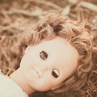 doll lying in a woodland floor, one eye open