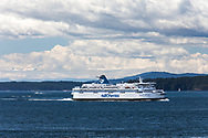 The BC Ferries vessel Spriit of Vancouver Island (built in 1994)  travels through Trincomali Channel on the way to Tsawwassen from Victoria (Swartz Bay).  Photographed from Village Bay at Mayne Island, British Columbia, Canada.  Mountain peaks in the clouds (background, left) are in the Olympic Range.
