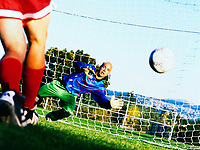 Goalkeeper in front of net diving for a soccer ball in mid air.