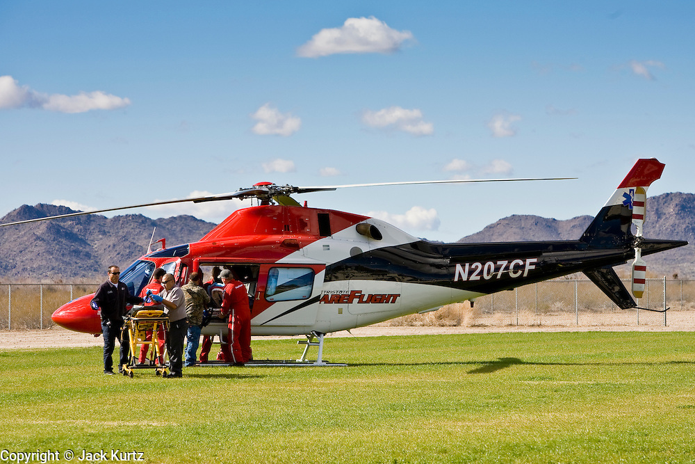 24 JANUARY 2010 -- WENDEN, AZ:  Paramedics hustle a patient complaining of a chess pains to a waiting medevac helicopter in Salome. The patient was one of hundreds of people who fled flood waters in Wenden. Wenden was slammed by its second 100 year flood in 10 years on Thursday night when water raced through Centennial Wash and into the small town in La Paz County west of Phoenix. Most of the town's residents were evacuated to Red Cross shelters in Salome, about 5 miles west of Wenden.    PHOTO BY JACK KURTZ