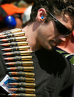 A man carries a band of ammunition on his shoulder on the firing line at the Knob Creek Machine Gun Shoot near West Point, Kentucky April 9, 2005. Thousands of machine gun and military hardware enthusiasts attended the event held each year over weekends in the spring and fall.