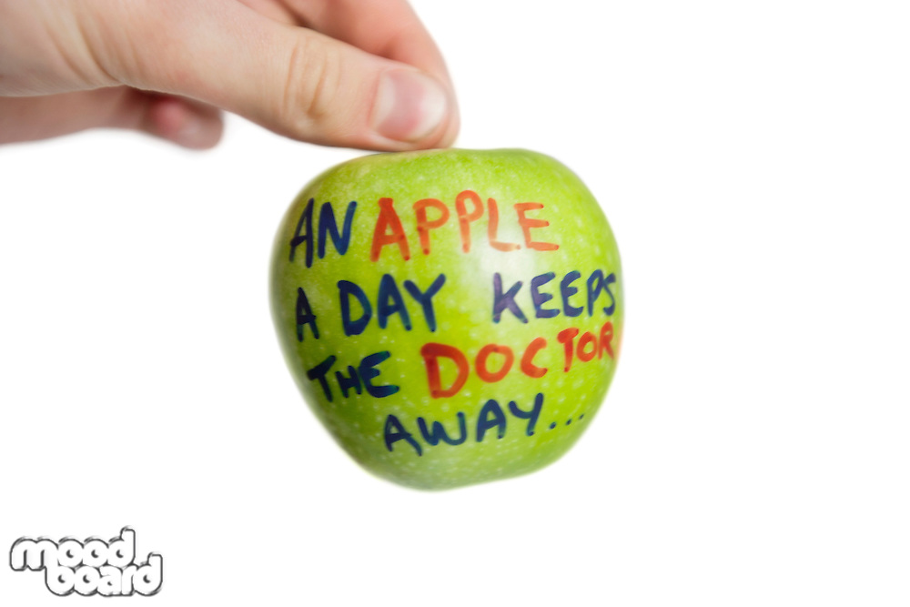 Cropped image of hand holding a granny smith apple with sayings text over white background