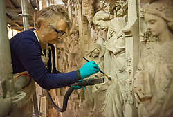 © Licensed to London News Pictures. 07/02/2018. WINCHESTER, UK. A conservator cleans a nativity image from the Great Screen at Winchester Cathedral, Hampshire, to remove dirt and dust from the 540-year-old stonework using soft brushes and hand-held vacuum cleaners as part of a programme of urgent repairs to the Cathedral's presbytery which has been carried out over the last three years. According to Cathedral records, this will be the first time that the Great Screen has been cleaned since the 1890s. Photo credit: ISABEL INFANTES/LNP