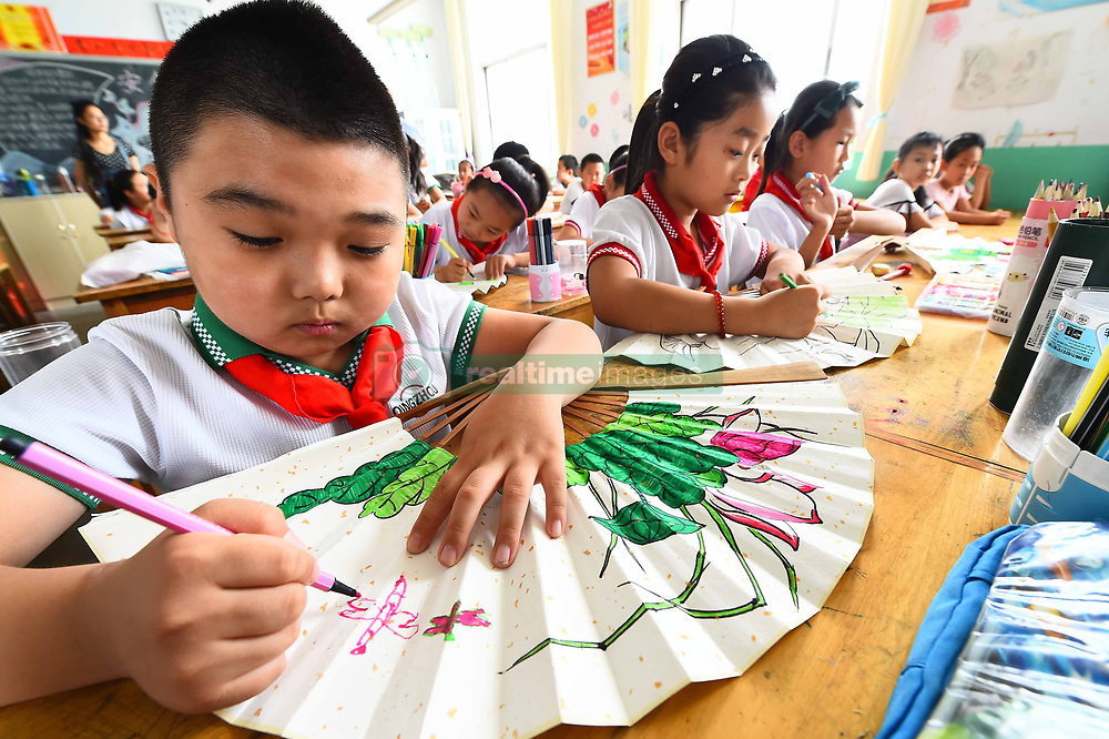 June 20, 2017 - Weifang, Weifang, China - Weifang, CHINA-June 20 2017: (EDITORIAL USE ONLY. CHINA OUT)..Pupils draw paintings on paper fans at a primary school in Weifang, east China's Shandong Province, June 20th, marking the solar term of summer solstice and experiencing traditional Chinese culture. (Credit Image: © SIPA Asia via ZUMA Wire)