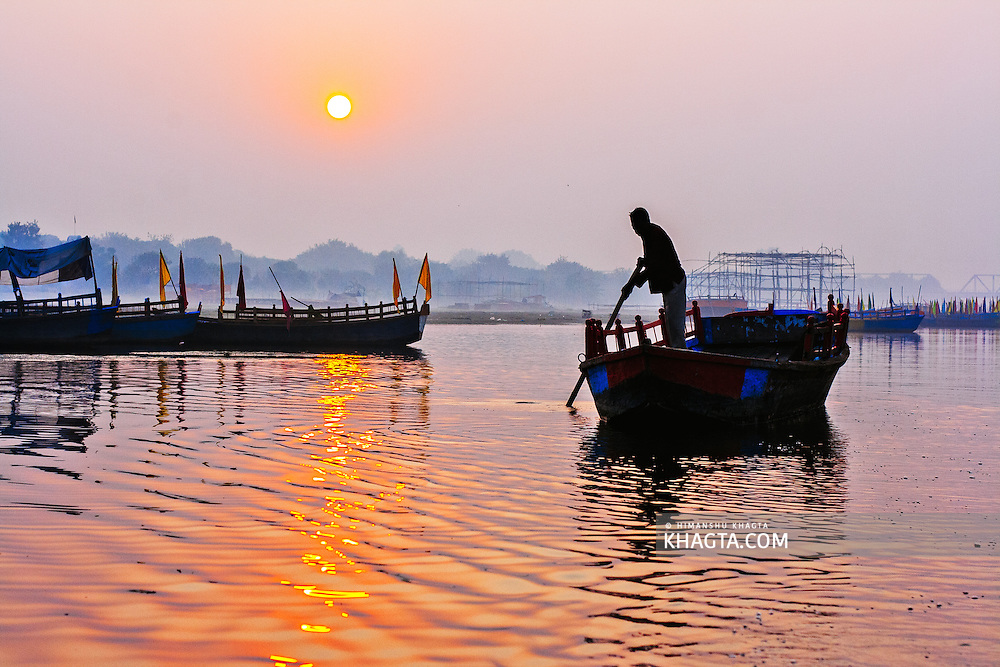 At the dawn of a morning, a boatman rowing his boat on Yamuna river in Mathura. Mathura is a sacred town situated on the banks of Yahuman river in Uttar Pradesh, northern India. The birthplace of the deity Lord Krishna. It is a pilgrimage site for Hindus.