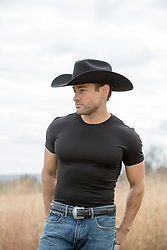 cowboy in a black tee shirt on a ranch