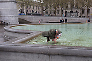A man climbs out of chemically-reated freezing fountain water  in Trafalgar Square, Westminster, on 9th April 2019, in London, England.