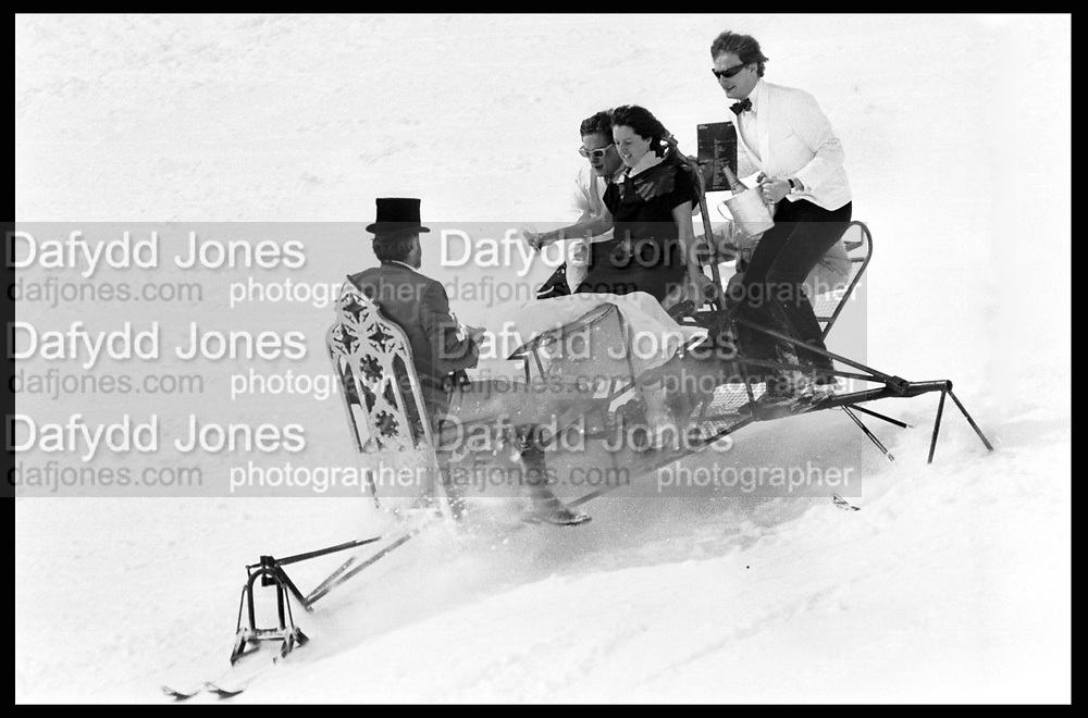 David Kirke, Tim Hunt, Nicky Slade and Lord Xan Rufus Isaacs going down on dining table, Dangerous Sports Club ski race. St. Moritz. 1983.