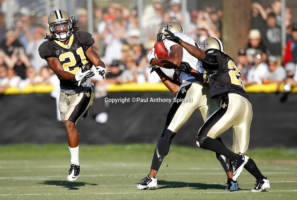 New Orleans Saints wide receiver Marques Colston (12) catches a pass while covered by Saints cornerbacks Patrick Robinson (21) and Tracy Porter (22) during the Saints west coast NFL training camp on Wednesday, August 24, 2011 in Oxnard, California. (©Paul Anthony Spinelli)