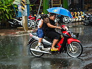 19 JANUARY 2016 - BURI RAM, BURI RAM, THAILAND: People on a motorcycle duck raindrops during an unseasonal thunderstorm in Buri Ram, Thailand.    PHOTO BY JACK KURTZ
