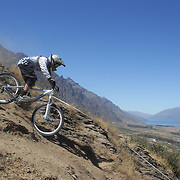 Alex Kennett from Waiotira in action during the New Zealand South Island Downhill Cup Mountain Bike series held on The Remarkables face with a stunning backdrop of the Wakatipu Basin. 150 riders took part in the two day event. Queenstown, Otago, New Zealand. 9th January 2012. Photo Tim Clayton