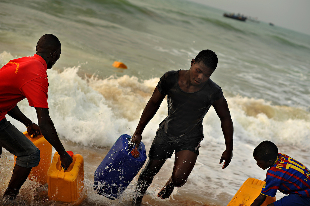 12-01-29  --  ANEHO, TOGO  --  Men and boys pull jerry cans full of fuel out of the Gulf of Guinea in Togo on January 29. Swimmers will tow the jerry cans -- and even 240/250 litre barrels -- to shore from Nigerian boats anchored just off shore, pictured at rear. Legally bought in Nigeria, the fuel is loaded onto boats which sail to Togo under the cover of night. The journey takes approximately 13 hours. Photo by Daniel Hayduk