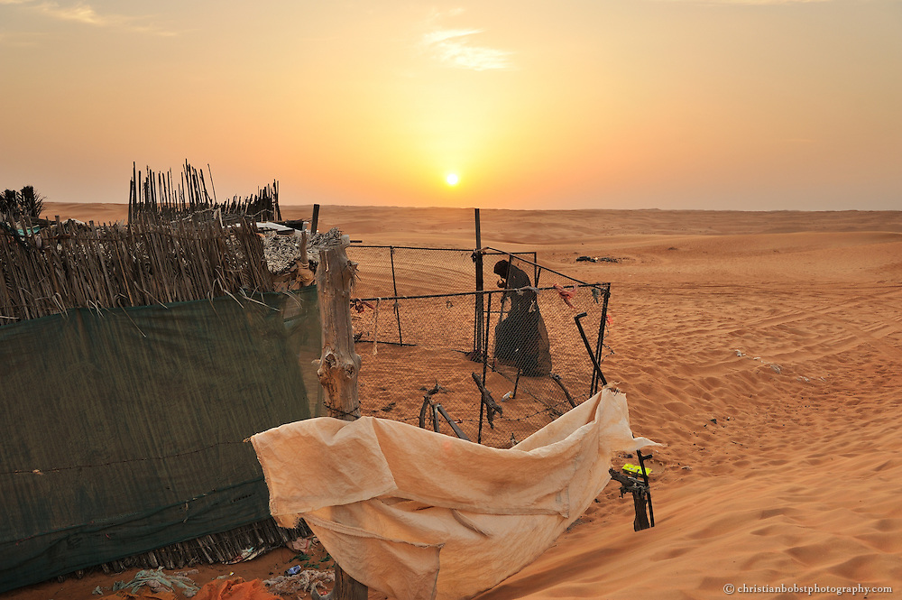A beduin women in front of their tent in the desert of Wahiba, sands, Oman, 2011