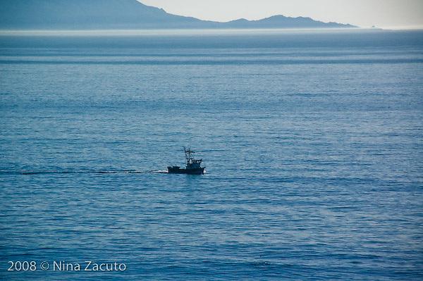 Lone boat tugs along the California coast.