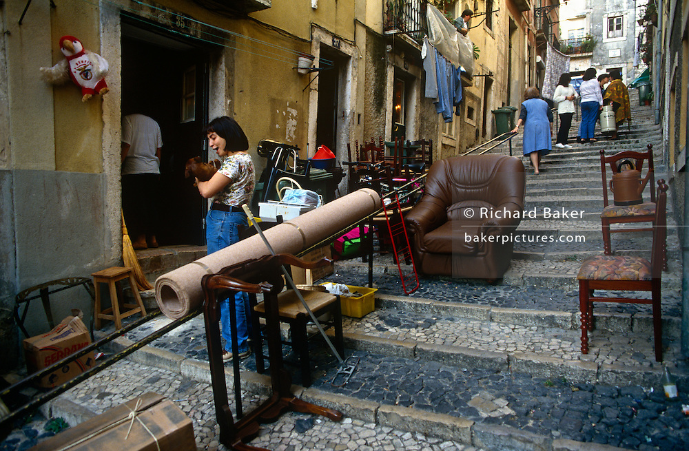 A young woman cuddles her pet dog in a steep, cobbled pedestrian street as her family moves house in Lisbon's Bica district.